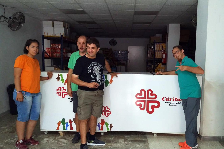 Les persones usuàries del Centre Obert Habilitare ABD Torrent, a València, donen aliments a la delegació de Càrites de la zona